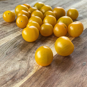 yellow cherry tomatoes on a board