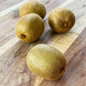 4 kiwi fruits on a wooden board