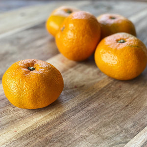 5 satsumas on a wooden board