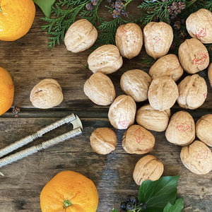 whole walnuts on a wooden board with foliage and satsumas