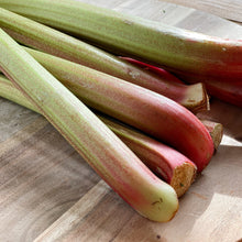 Load image into Gallery viewer, sticks of fresh rhubarb on a wooden board