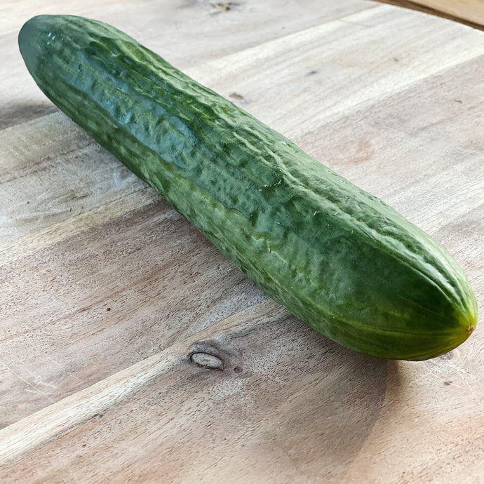 full sized cucumber on a wooden board