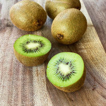 Load image into Gallery viewer, 4 kiwi fruits on a wooden board one cut open