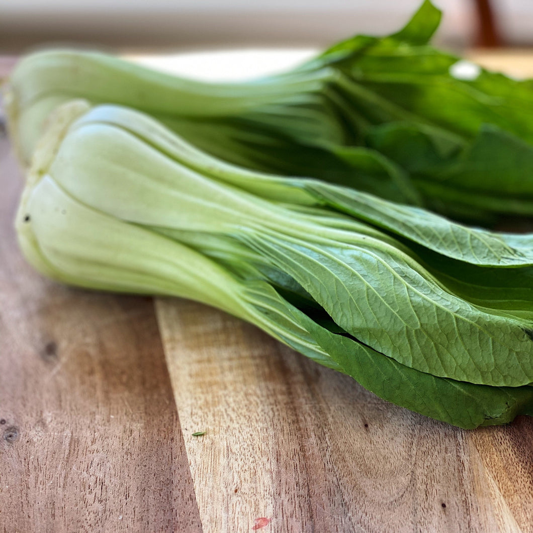 2 bulbs of pak choi on a wooden board