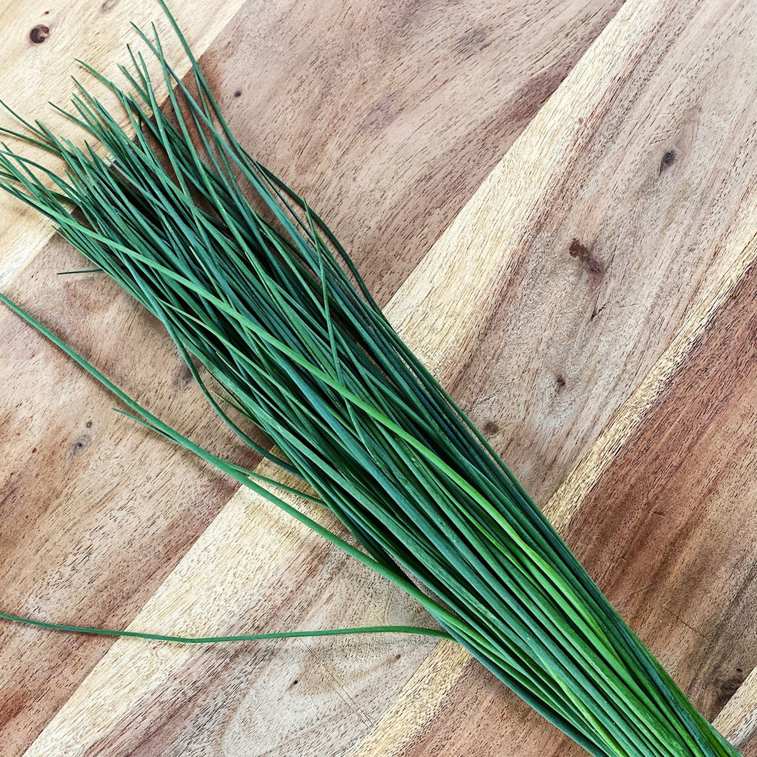 fresh chives on a wooden board
