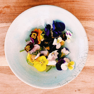 edible viola flowers in a pale blue bowl on a wooden board