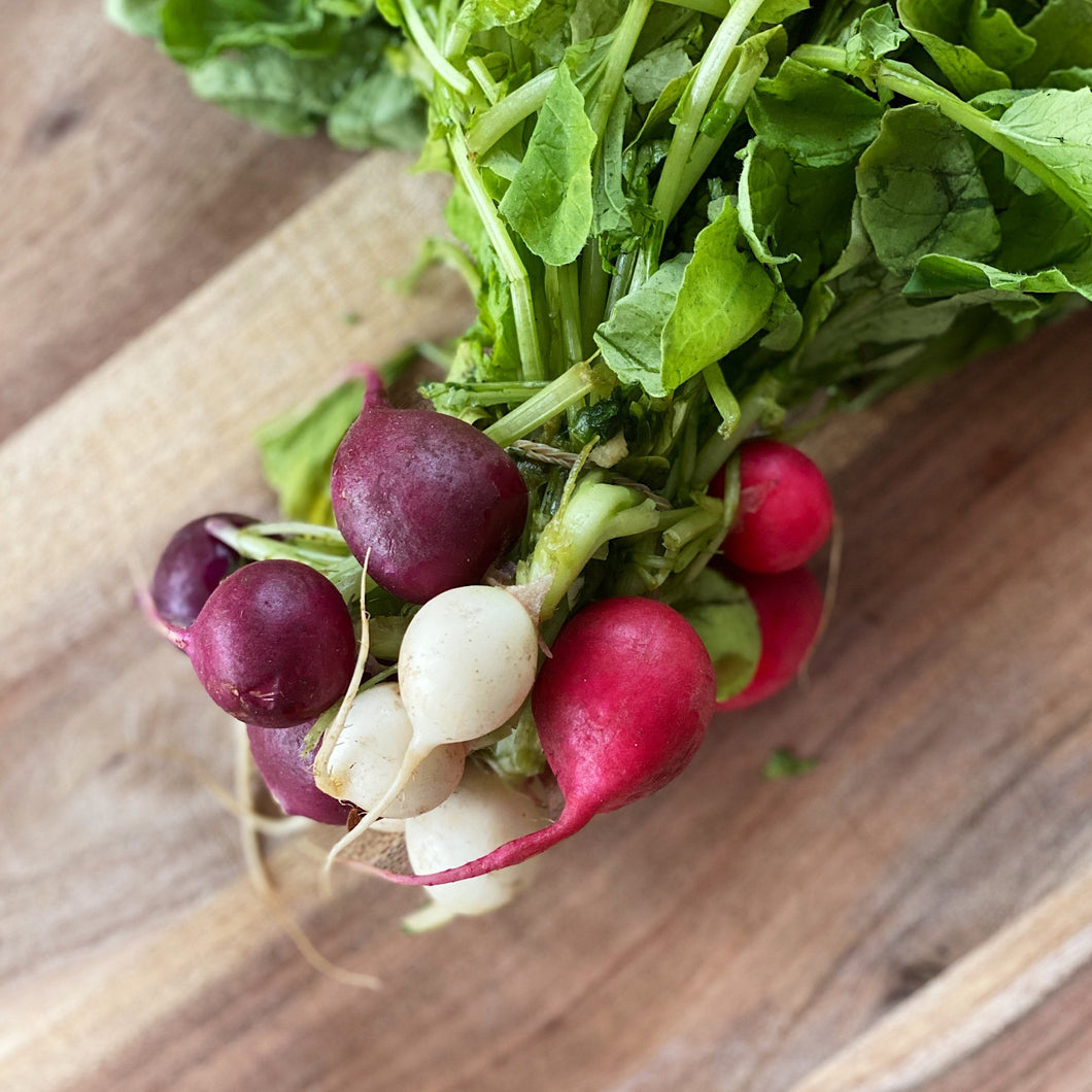 fresh Heritage radishes on a wooden board