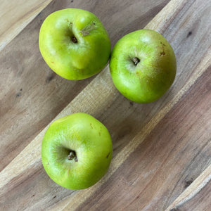 bramley cooking apples on a wooden board