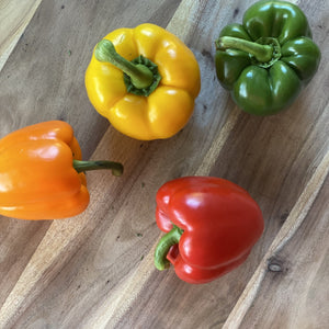 green yellow orange red peppers on a wooden board
