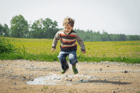 Little boy jumping in puddles