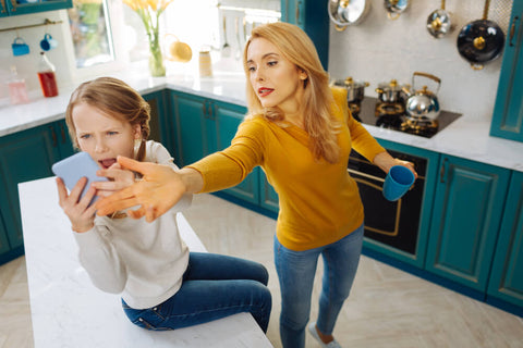Mother taking phone from girl