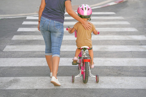 Mother helping child ride bike across the street