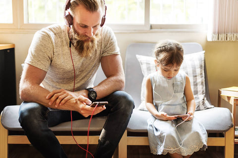 Dad and daughter listening to music on their phones