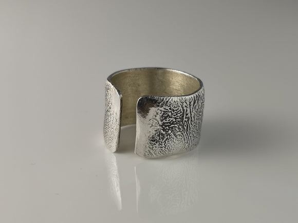 A handmade wide band sterling silver reticulated ring. The process of reticulation creates a truly earthy unique finish which is different every time.