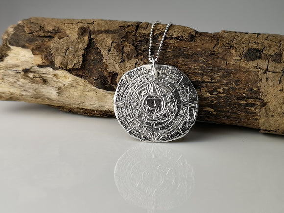 A Handmade fine silver pendant depicts the Mayan calendar. This Consists of three separate corresponding calendars creating wheels that work together.