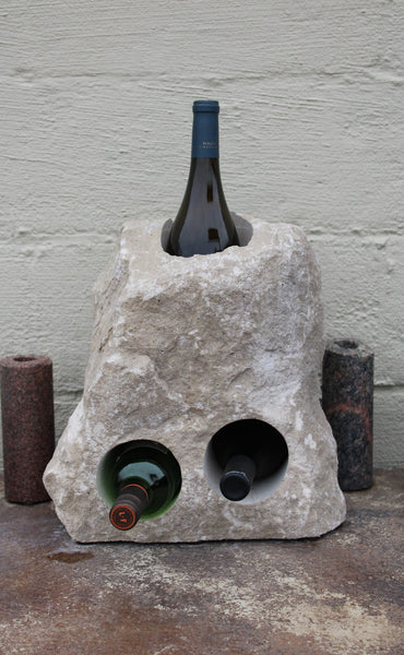 Triangular shaped Limestone wine rack with a white rough texture.  Stone has been drilled to hold 3 bottles of wine, one vertically near the top half of the stone acting as a chiller, and two horizontal side by side near the bottom half.  Bottom of stone has been cut flat.  Shown sitting atop a table  holding 3 bottles of wine.  Stone is approximately 15 inches tall.