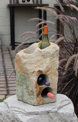 "Rough textured Limestone Wine Rack with two vertical holes and two horizontal holes, showing 3 bottles of wine, all set atop a boulder pedestal.  17"" tall"