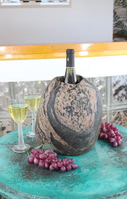 "Oval shaped Granite stone wine chiller, 11"" tall with one 3-1/2""  diameter hole 8"" deep and holding one bottle of wine, set upon table with grapes and two glasses of white wine."