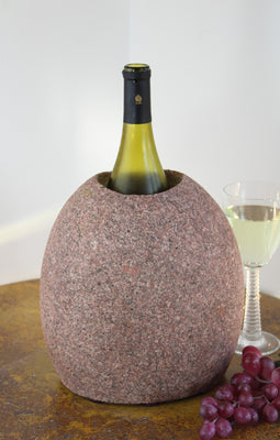 "Oval Pink Granite Stone Wine Chiller 9"" tall with one  large vertical hole, showing one bottle of wine, set atop small table with red grapes and a glass of white wine."