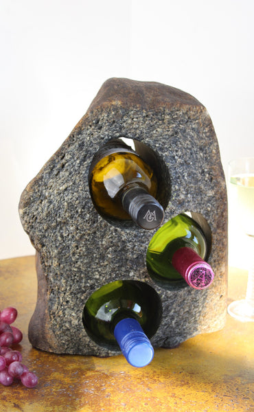 Grey-Brown Granite Stone Wine Rack holding 3 bottles of wine horizontally,  set atop a small table with red grapes and a glass of white wine.