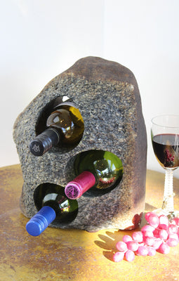Grey-Brown Granite Stone Wine Rack holding 3 bottles of wine horizontally,  set atop a small table with red grapes and a glass of red wine.