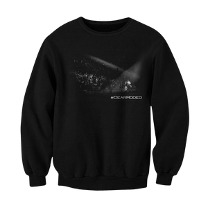 "Black pullover sweater. Print is black and white picture of Cody onstage playing in front of fans. Underneath the right side of the photo says ""#DEARRODEO"""