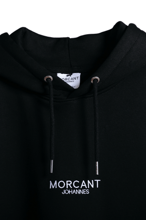 Detail shot of the black organic Morcant hoodie, showing the matching coloured drawstrings with metal tips and the featured Morcant Johannes embroidery.