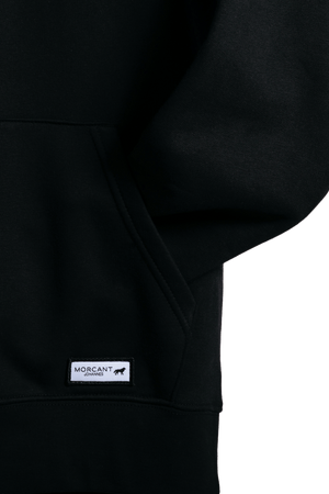 Detail shot of the black organic Morcant hoodie, showing the pocket quality and the featured Morcant patch.