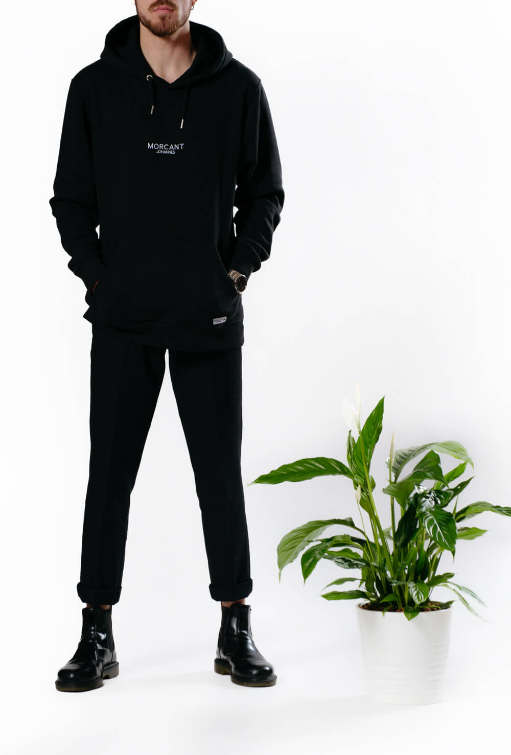 Male model wearing the black organic Morcant hoodie, paired with slim black suit trousers and a pair of Dr. Martins Chelsea boots.