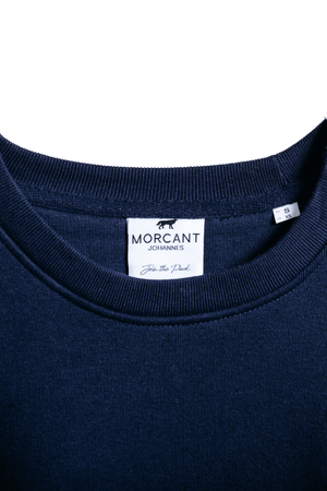 Detail image of our navy organic Morcant sweater, showcasing the Morcant inner label.