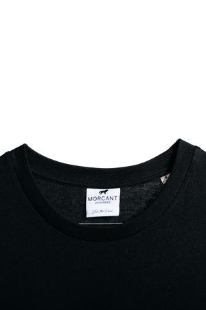 Detail image of our black organic Morcant t-shirt, highlighting the inner Morcant label and deep black tone.