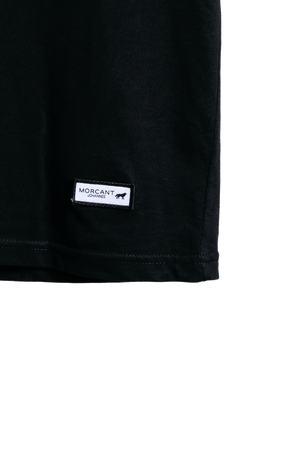 Detail image of our black organic Morcant t-shirt, showing the minimal Morcant brand patch.