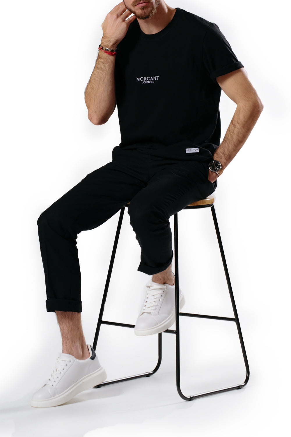 Male model wearing our black organic Morcant t-shirt, in a relaxed unisex fit, paired with slim fit black suit trousers and a white minimal sneaker.