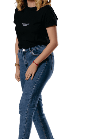 Female model wearing our black organic Morcant t-shirt, in a relaxed unisex fit, tucked into a pair of slim fit blue jeans.