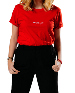 Female model wearing our red organic Morcant t-shirt, in a relaxed unisex fit, tucked into black tapered cigarette trousers.