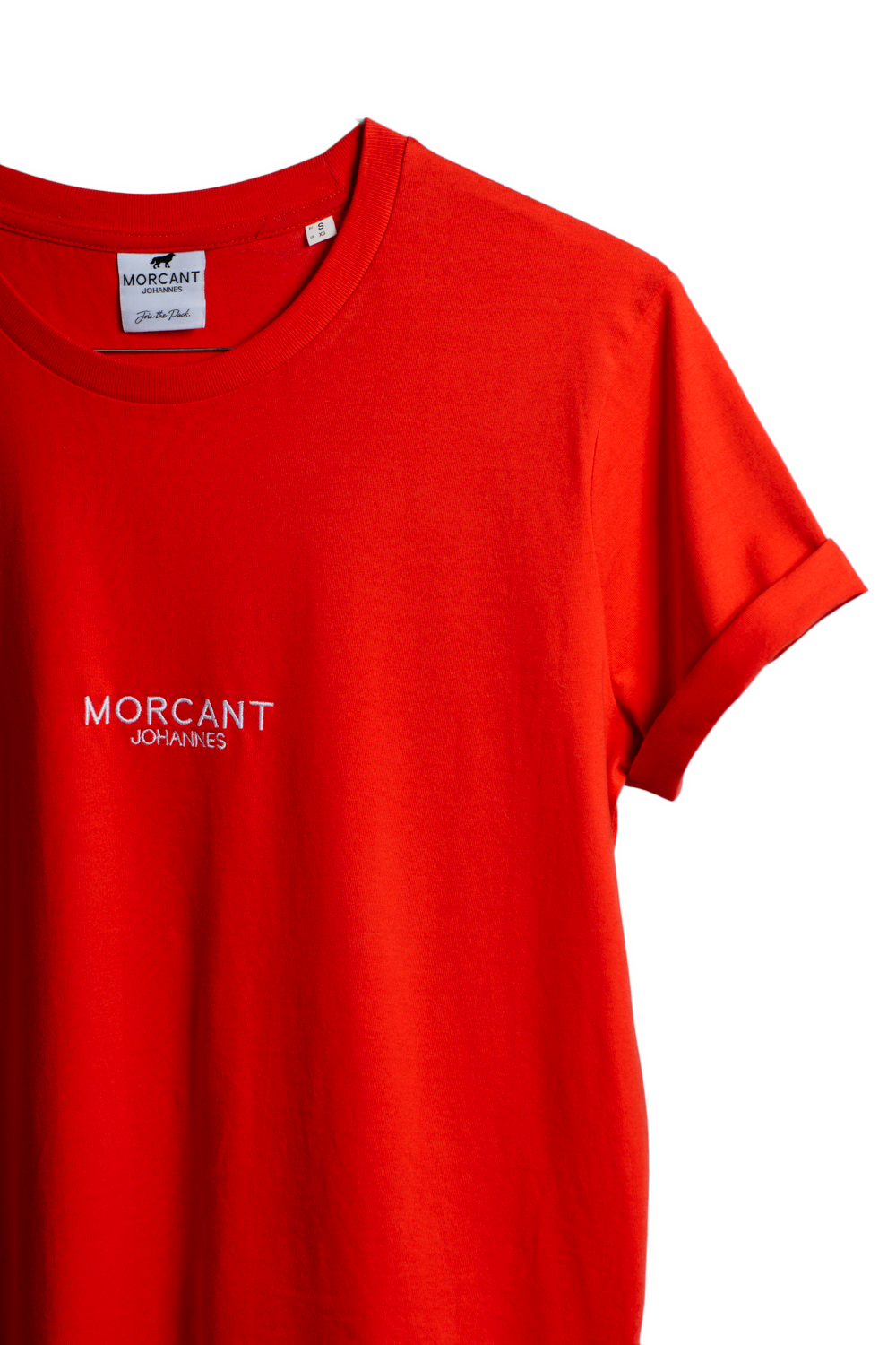 Detail image of our red organic Morcant t-shirt, displaying the right hand silhouette of the brightly coloured garment.