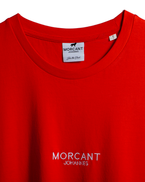 Detail image of our red organic Morcant t-shirt, magnifying the minimal Morcant Johannes embroidery and the Morcant inner label.