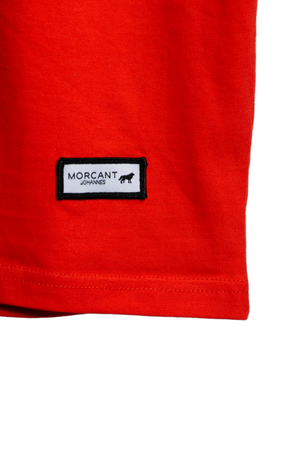 Detail image of our red organic Morcant t-shirt, spotlighting the minimal branded Morcant patch and the bright red tone.