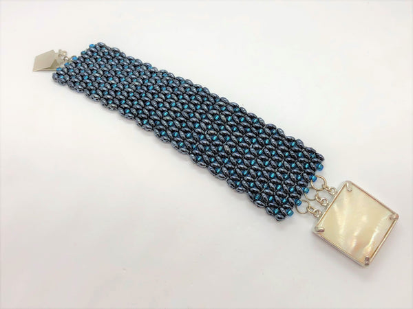 Gunmetal and electric blue X&O handsewn bracelet with a shell clasp