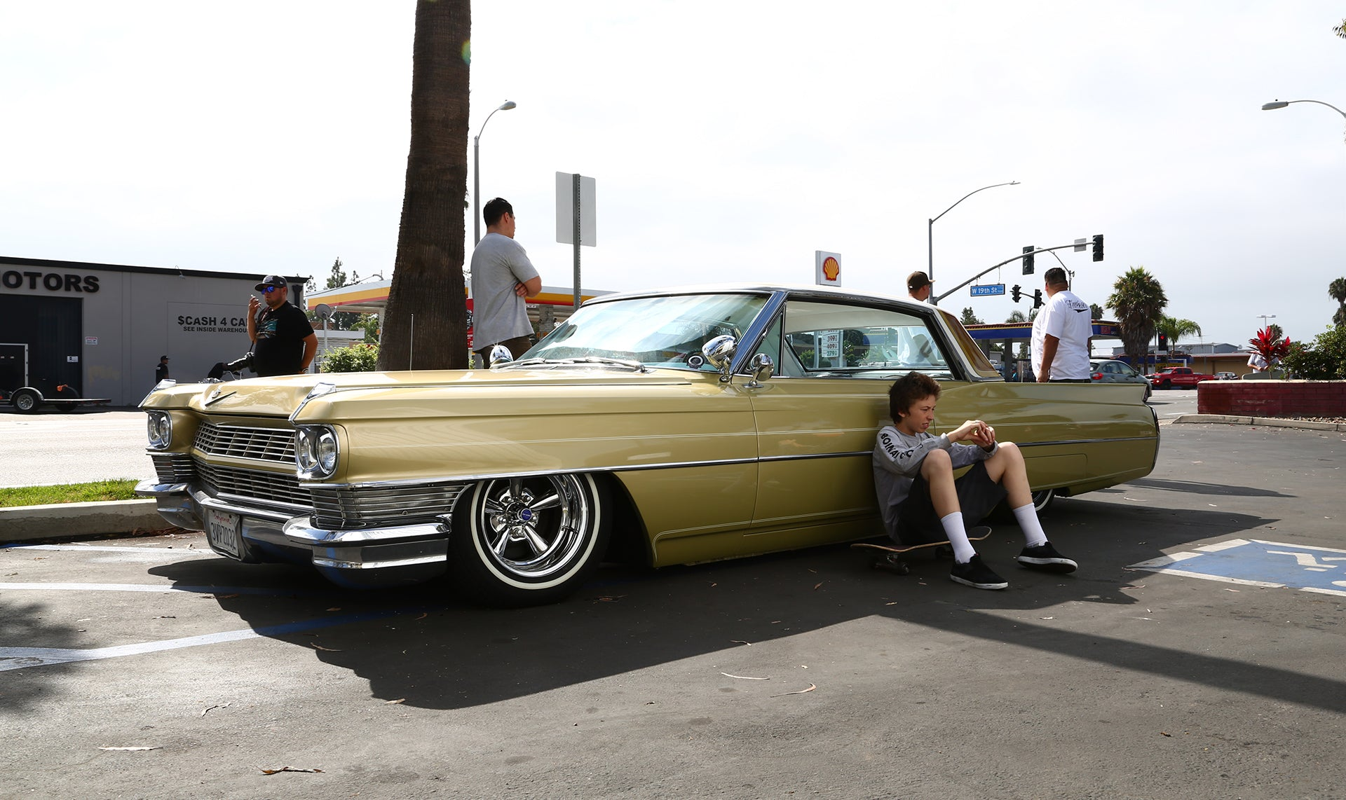 Kid relaxes up against a Cadillac at Legacy Carshow