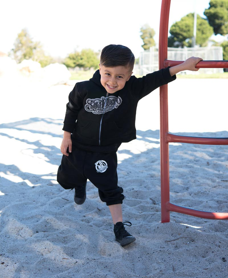 Suavecito OG Sweatsuit young boy on playground smiling