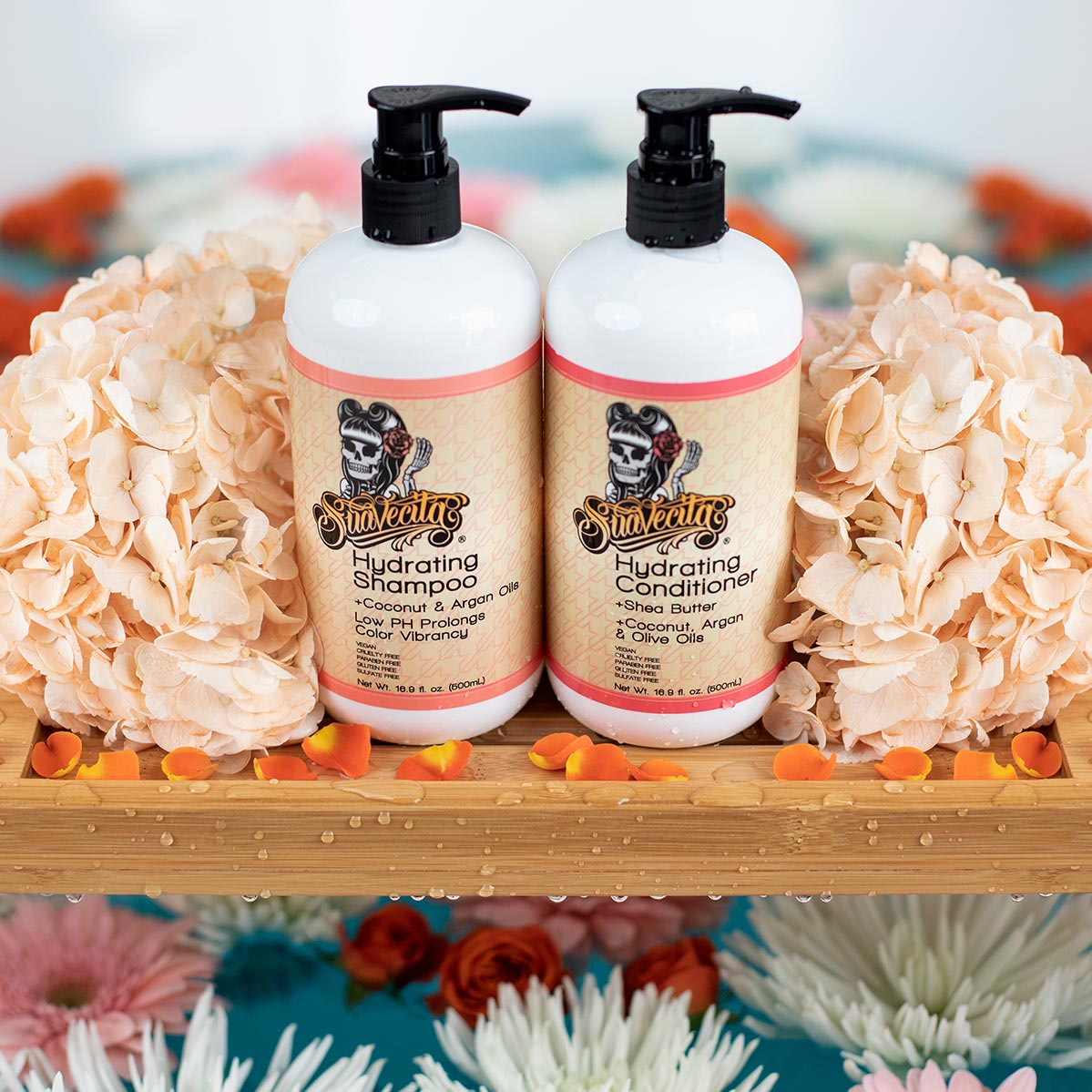 Suavecita Hydrating Shampoo and Conditioner on a bath tray surrounded with flowers
