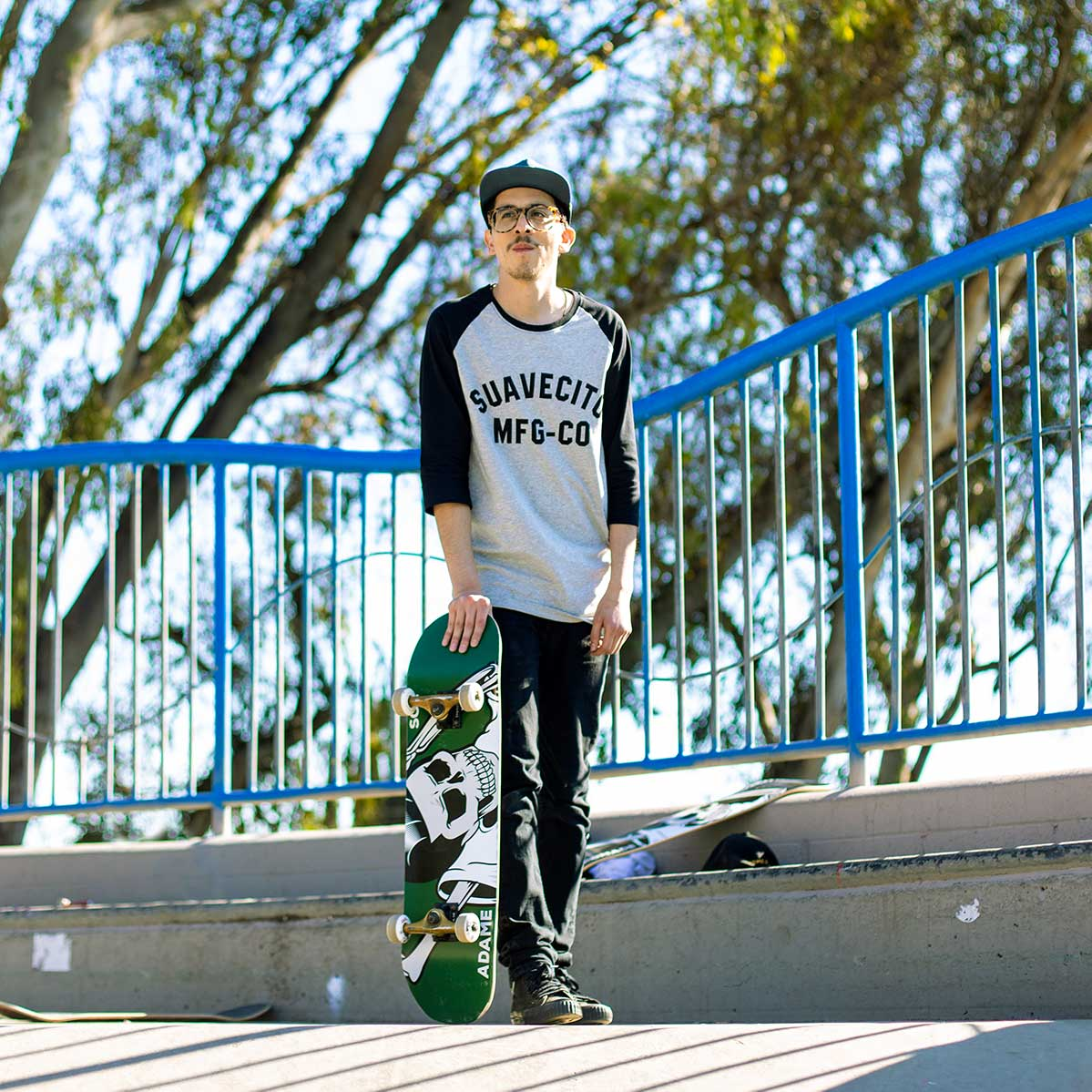 Skater wearing Suavecito grey baseball tee with black sleeves holding a green Suavecito skate deck