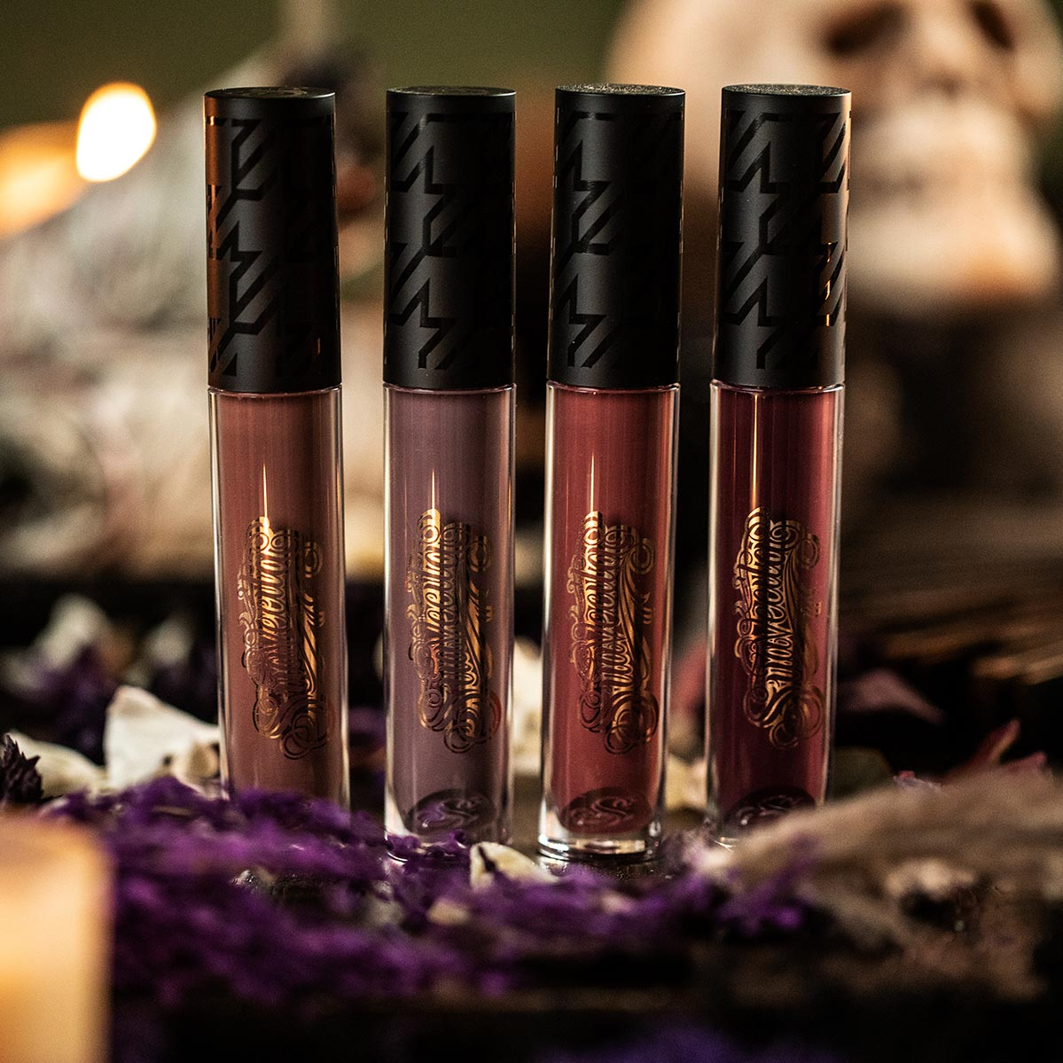 Suavecita Spellbound Lipgrip Collection on a table of dried flowers and sage
