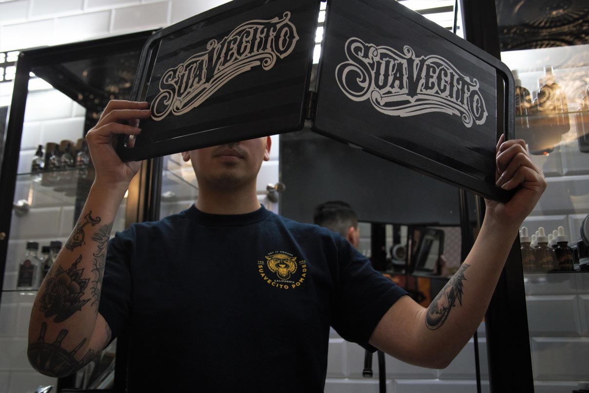Man Holding Up Suavecito Barber Mirror Looking at Hair