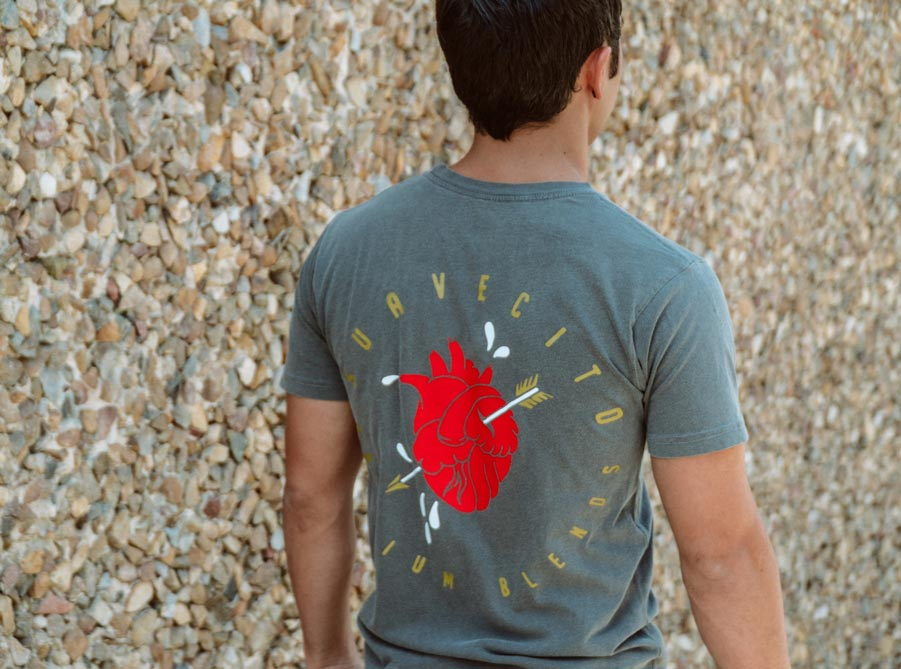 Man wearing Suavecito Heart and Arrow Tee Shirt with back graphic