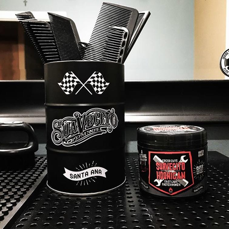 Suavecito and Hoonigan Pomade Can with a bigger Suavecito Can Holding Brushes