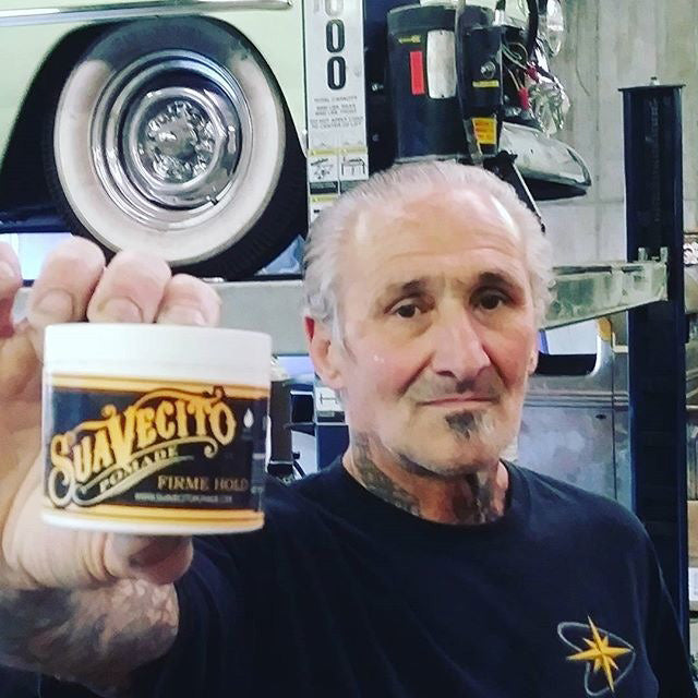 Suavecito OG pomade with a mechanic in a car garage