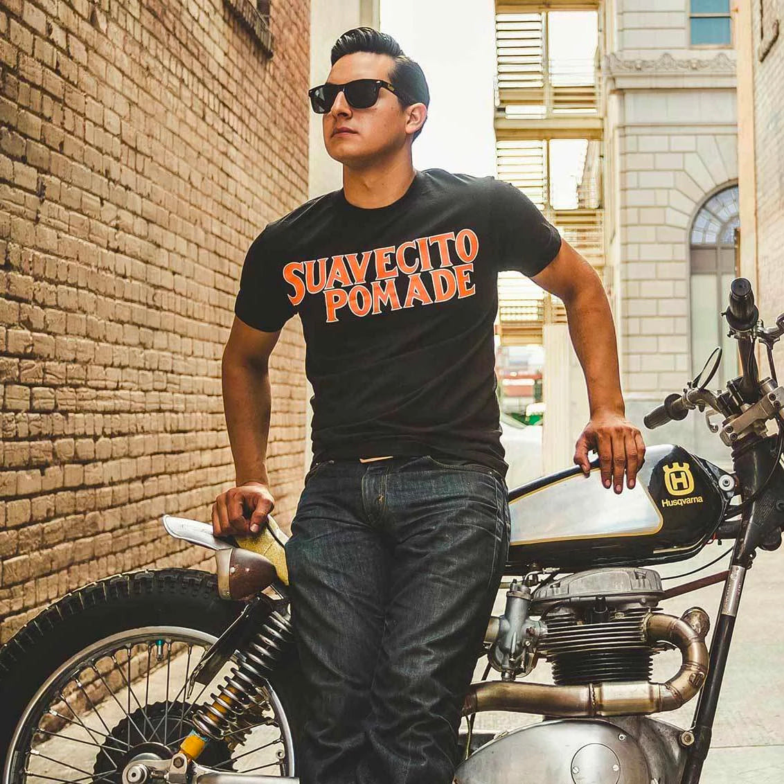 You man sitting on motor cycle wearing a Suavecito shirt