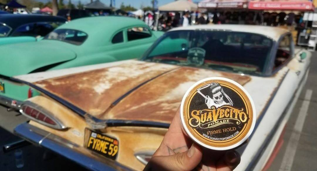 can of suavecito pomade in front of old classic cars at show